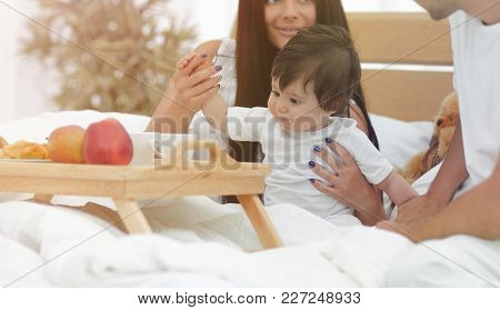 Family taking the breakfast on the bed in the bedroom
