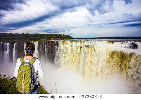 Energetic woman with a tourist backpack watching waterfalls the Devil's Throat. Concept of active and extreme tourism