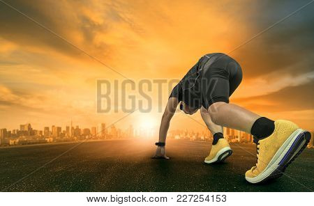 Young Man Approaching For Running Start On Wide Space Field Witha Beautiful Sunset Sky