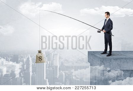 Businessman fishing sack of currency from the cityscape concept