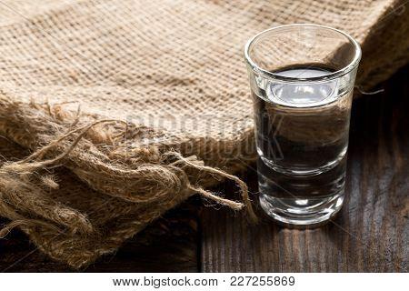 German Hard Liquor Korn Schnapps In Shot Glass With Burlap Sack On Rustic Wooden Table