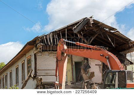 Building Demolition With Hydraulic Excavator. Dismantling An Old Residential House.