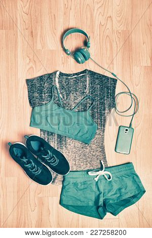Gym clothes fitness outfit. Matching clothing for girl training at home with headphones and phone to listen to music, , sports bra, shorts in blue and black running shoes.