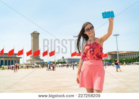 Asian tourist woman taking selfie photo with phone in Beijing, China. Asia travel famous destination girl holding cellphone visiting Tiananmen Square, popular tourism attraction. Summer vacation.