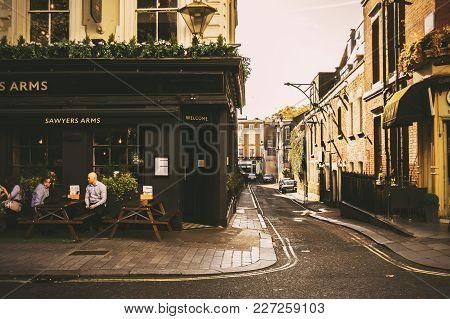 London, England - October 25 2017: Old Fashioned Style London Corner Pub And Street Life. Warm Sunny
