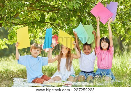 Children of creative craft group hold colorful cartons high in the park