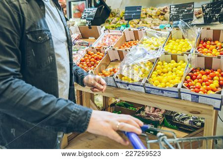 Man Seek Vegetables In Supermarket Stand Near Shelf With Tomatoes