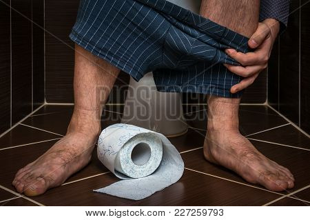 Man Suffers From Diarrhea Is Sitting On Toilet Bowl And Toilet Paper Roll Near His Legs