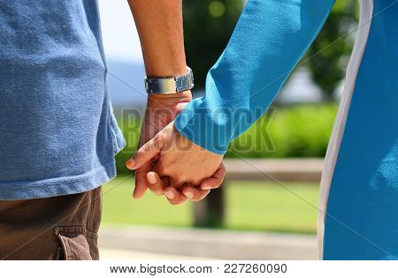 Happy Couple Holding Hands While Walking In A Park