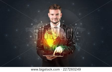 Spectacled businessman with global hologram concept and tablet on his hand