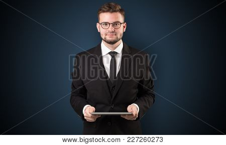 Handsome spectacled businessman holding a tablet with dark background