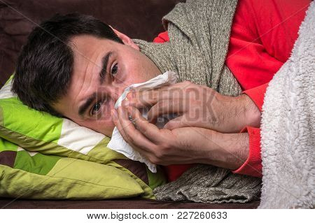 Sick Man Having Flu And Blowing Her Runny Nose At Handkerchief