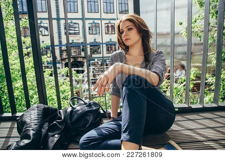 Pensive Young Woman Sitting On The Balcony