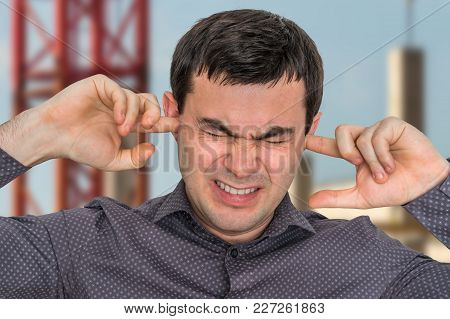 Man Closes Ears With Fingers To Protect From Loud Noise - Excessive Sound