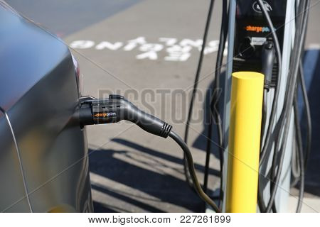 Costa Mesa CA - 2/17/2018: Electric Car being recharged in a parking lot. Electric Vehicles are earth friendly and do not use gasoline.