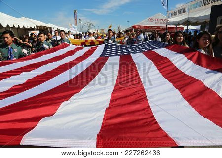 Costa Mesa CA 2/17/2018:  Giant American flag proudly being carried in a parade during the 2018 TET Festival aka the Lunar New Year. Lunar New Year of the Dog.