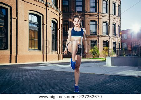 Young Fitness Woman Doing Warm-up Exercise Before Running Stretching Her Leg By Performing Knee To C