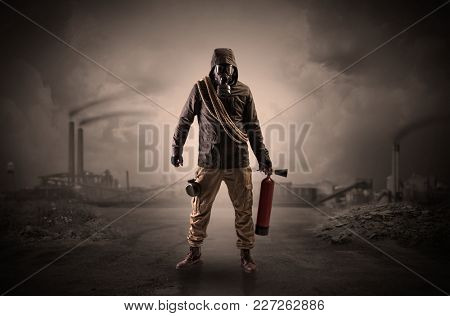 Gas masked survival man coming with arms on his hand  in a demolished dark environment