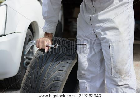 Professional Young Mechanic In Uniform With Spare Tires And Wrench For Fixing Car At The Repair Gara