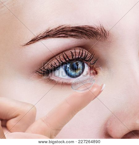 Contact Lens On Index Finger Near Blue Female Eye. Eyesight And Ophthalmology Concept.