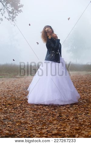 Bride In A Wedding Dress And A Leather Jacket With A Closed Face