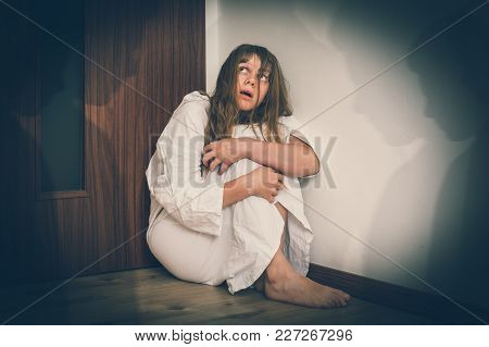 Scared Woman With Schizophrenia Sitting In The Corner At Room With People Shadows - Hallucinations A