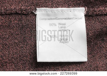 Fabric Composition Clothes Label On Brown Knitted Background Closeup