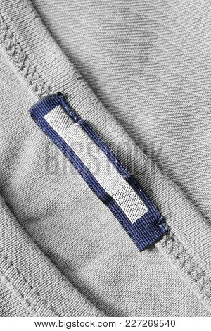 Blank Textile Clothes Label On Knitted Cotton Grey Background