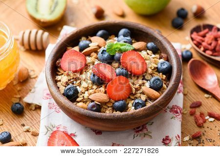 Granola Bowl With Fresh Strawberries, Blueberries, Dried Goji Berries And Almonds On Wooden Table. C