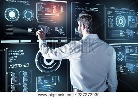 Attentive Specialist. Calm Concentrated Young Programmer Standing In Front Of A Futuristic Screen An