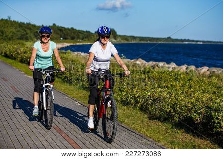 Women riding bicycles at seaside