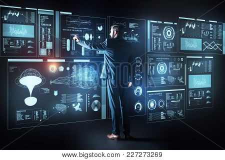 Giant Screen. Clever Experienced Qualified Programmer Wearing An Elegant Suit And Touching The Scree