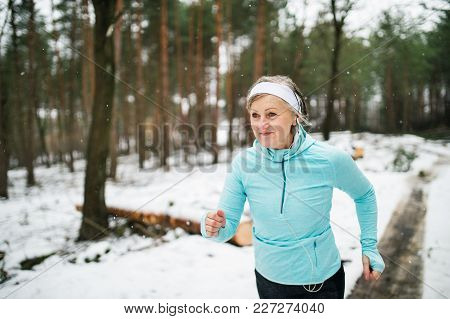 Senior Woman Jogging Outside In Winter Nature.