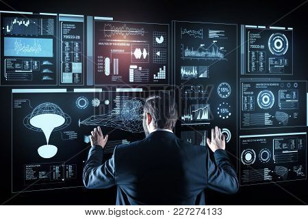 Modern Technologies. Calm Attentive Smart Programmer Working With A Futuristic Device And Feeling Im