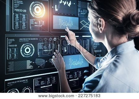 Clever woman. Experienced qualified young programmer working in a big company and looking interested while touching the screen of her futuristic device poster