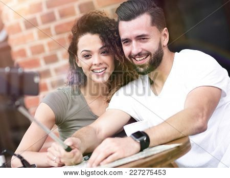 Happy cheerful couple sitting down at a cafe and making selfie