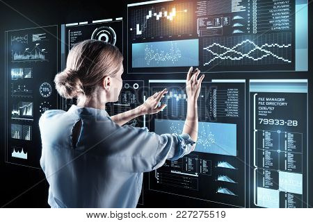 Gentle Touch. Beautiful Young Smart Woman Touching The Futuristic Screen With The Fingers And Though
