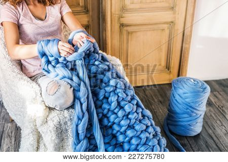 Small Business Of A Young Woman. Unrecognizable Woman Hand-knitting A Woollen Blanket.