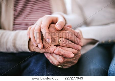 Unrecognizable Teenage Girl With Grandmother At Home, Holding Hands. Family And Generations Concept.