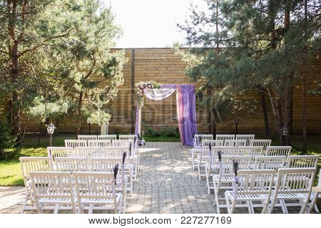 Purple Wedding Arch Decorated With Flowers, Lilac And Pink Material. The Beautiful Platform For A We