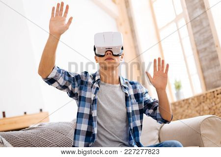 Virtual Reality. Concentrated Well-built Stylish Adolescent Wearing A Vr Headset And Relaxing While