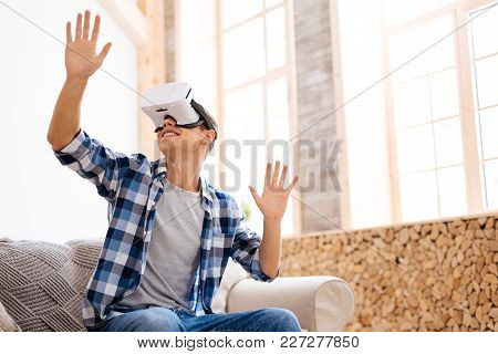 Spare Time. Exuberant Well-built Stylish Adolescent Wearing A Vr Headset And Relaxing While Sitting