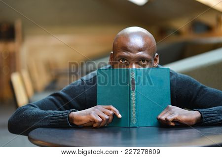 A Young Arican Man Is Reading A Book In A Room At A Table. Student, Businessman. Low Key Photo