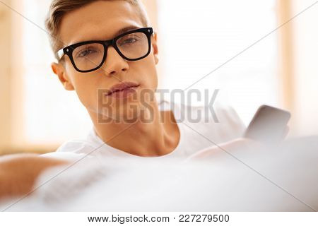 Bad Day. Handsome Worried Unsmiling Young Man Wearing Glasses And Holding His Phone And Feeling Sad