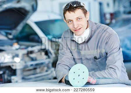 auto repairman with grinding machine