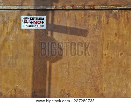 No Parking Sign On Rusty Metal Garage Door With Shadows Of Light Post And Street Signs In Mexico Cit