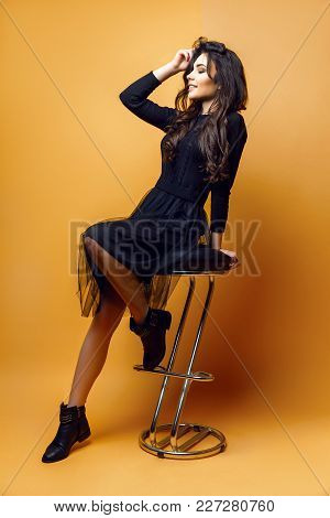 Pretty Young Woman In Black Dress Sitting On Chair On Yellow Background.