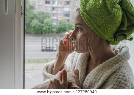 A Lonely Girl With A Cat And A Phone Sits On The Window