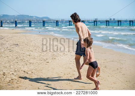 Dad And His Son Run Along The Beach To The Pier In Swimming Trunks. Beach Holiday