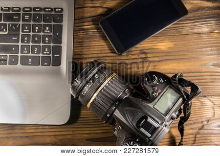 Laptop, Smart Phone And Photo Camera On Wooden Background